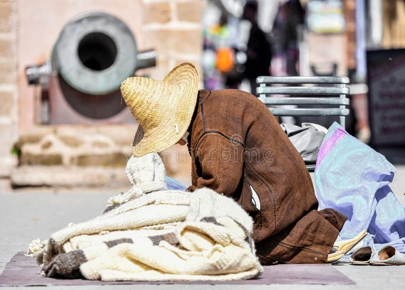 Een oude slechte mens die de kegel wevende sweater dragen van de riethoed terwijl het zitten op kant van de weg, Marokko stock afbeeldingen