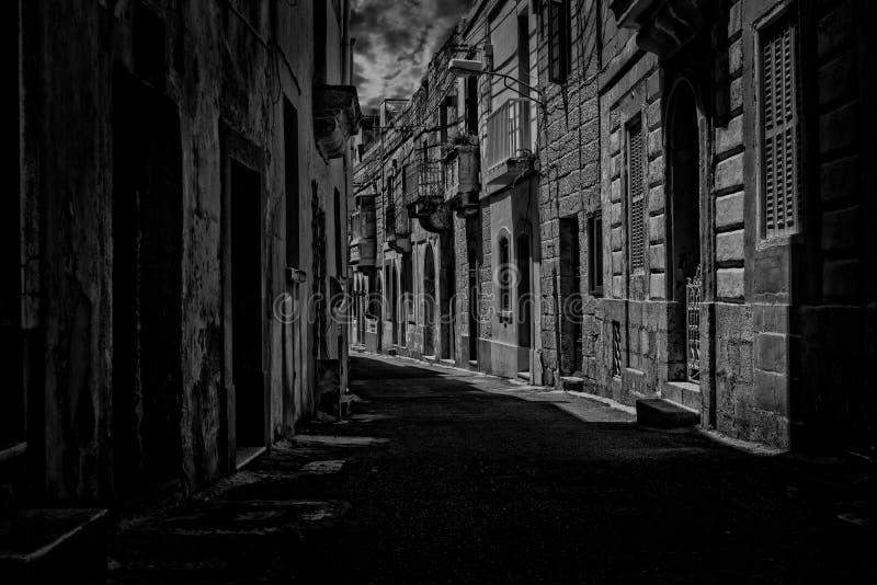 Een oude smalle straat in Rabat, Malta in zwart-wit stock afbeeldingen