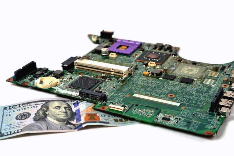 Een oude spaander van laptop ligt op een rekening van honderd dollars, royalty-vrije stock fotografie