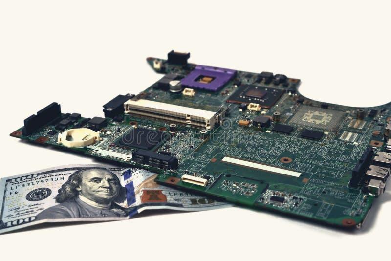 Een oude spaander van laptop ligt op een rekening van honderd dollars, royalty-vrije stock afbeeldingen