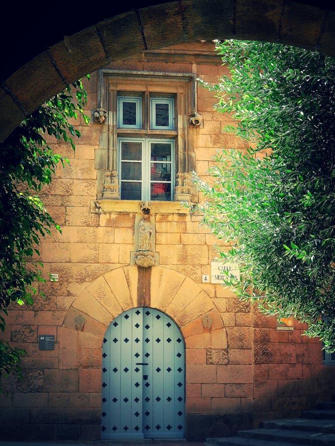 Een oude Spaanse binnenplaats met een venster en een oude deur stock foto's