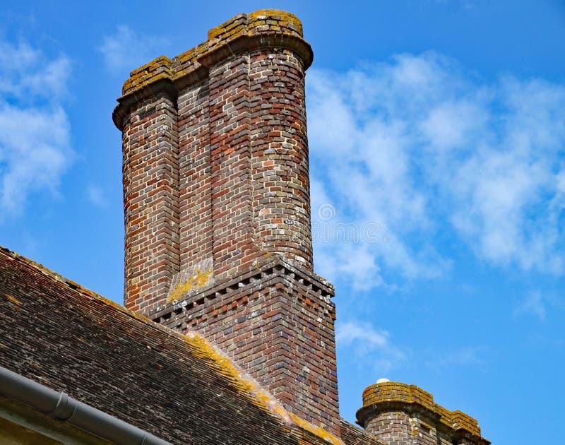Een oude stapel van de baksteenschoorsteen boven op een oud Engels huis stock fotografie
