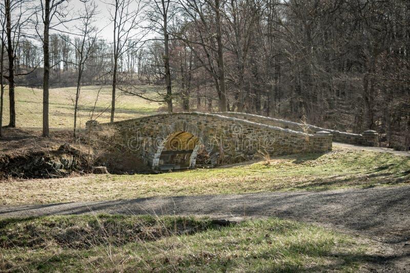 Een oude steenbrug die over een kleine kreek in het bos leiden stock foto's