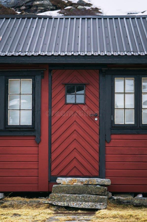 Een oude uitstekende houten voordeur met venster op een rood buitenhuis Voorgevelbuitenkant Retro Skandinavisch platteland royalty-vrije stock afbeelding