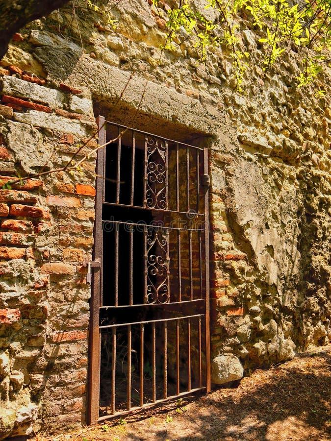 Een oude vervaardigde irndeur in een rottende Roman muur royalty-vrije stock foto