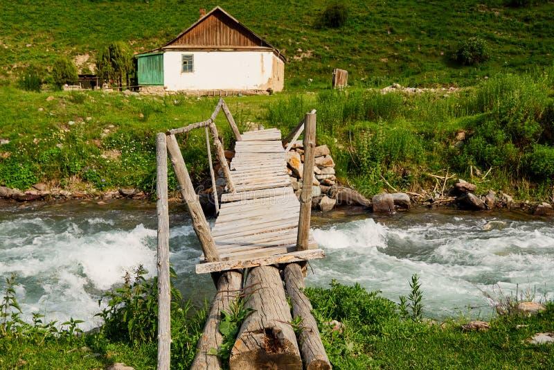Een oude vervallen die boerderij door bergen wordt omringd en een bergrivier met een houten oude brug royalty-vrije stock foto