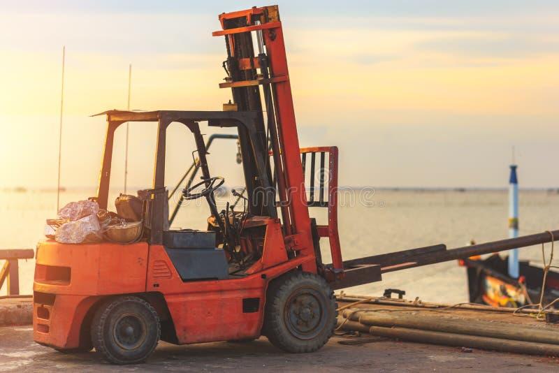 Een Oude Vorkheftruck die lading op een weg vervoeren dichtbij het overzees met zonsondergangtijd stock afbeelding