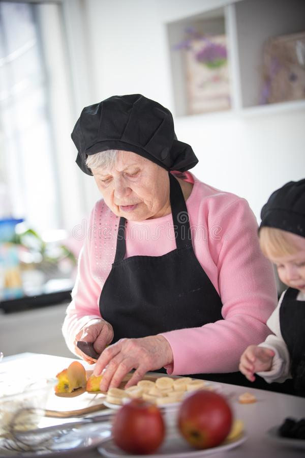 Een oude vrouw die een appel op stukken met een klein meisje in de keuken snijden stock afbeelding
