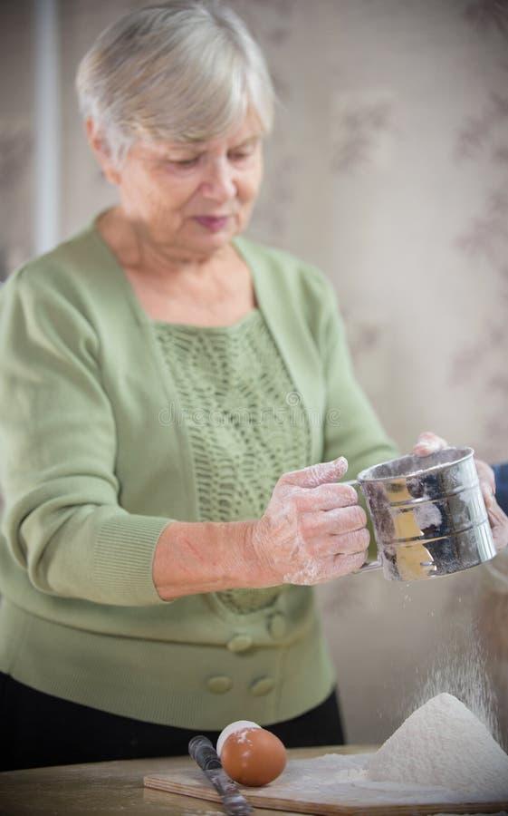 Een oude vrouw die kleine appeltaarten maken Het ziften van de bloem stock foto