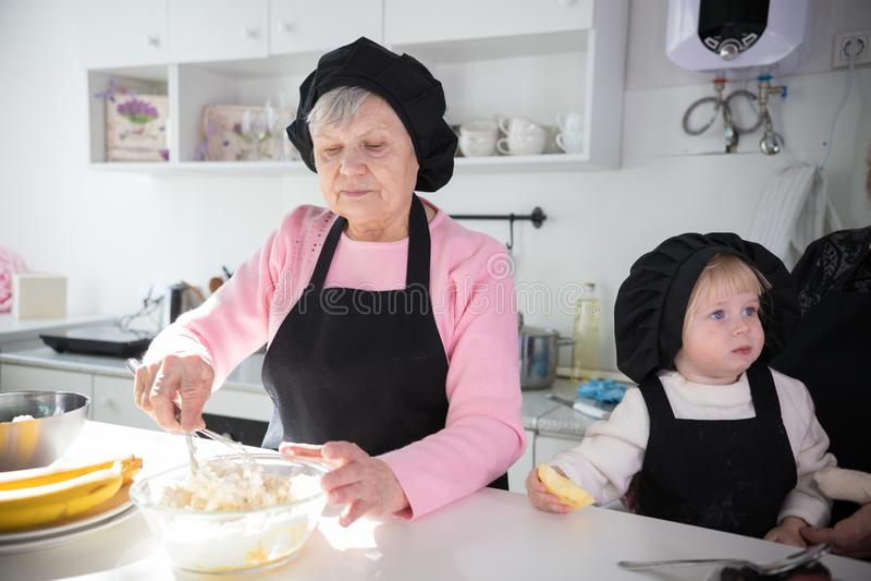 Een oude vrouw die pannekoeken met een klein meisje in de keuken maken Het maken van deeg in de kom royalty-vrije stock foto's