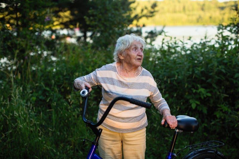 Een oude vrouw die zich met een Fiets op de straat bevinden royalty-vrije stock afbeeldingen
