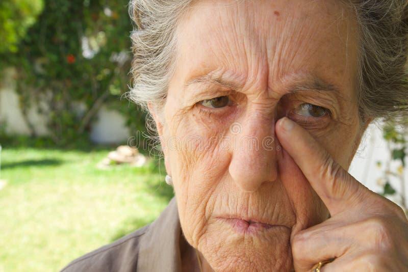Een oude vrouw droogt de scheuren van haar gezicht royalty-vrije stock afbeeldingen