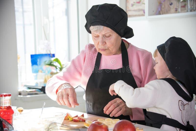 Een oude vrouw met een klein meisje in de keuken die vruchten voor het dienen voorbereiden royalty-vrije stock afbeelding
