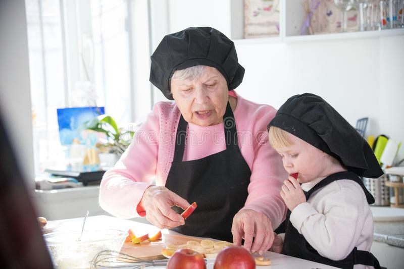 Een oude vrouw met een klein meisje in de keuken Een klein meisje eet een stuk van appel royalty-vrije stock foto's
