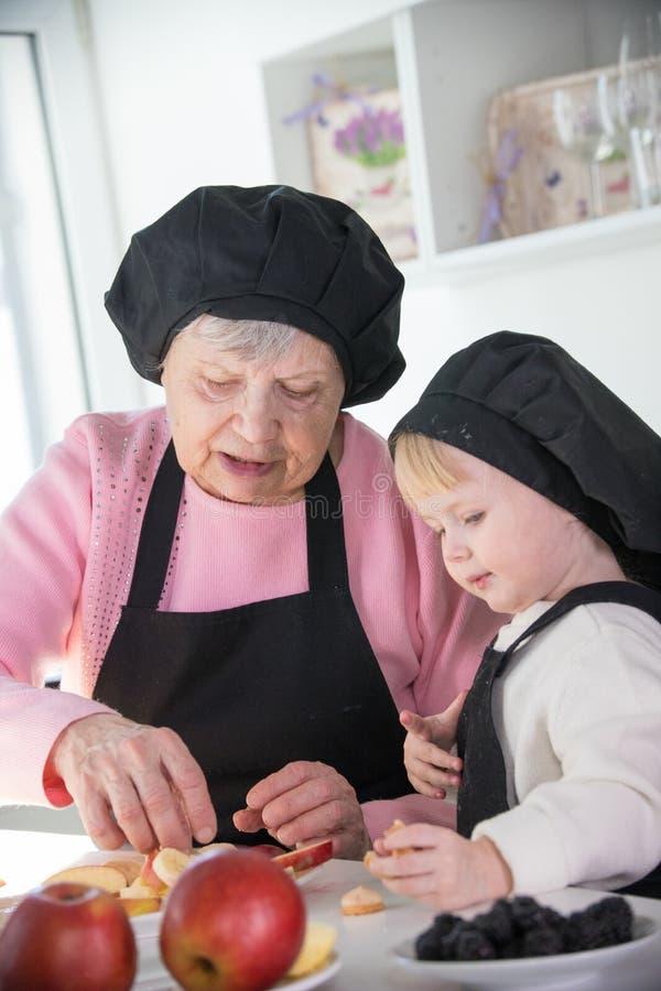 Een oude vrouw met een klein meisje die zich in de keuken bevinden die vruchten voor het dienen voorbereiden royalty-vrije stock foto's