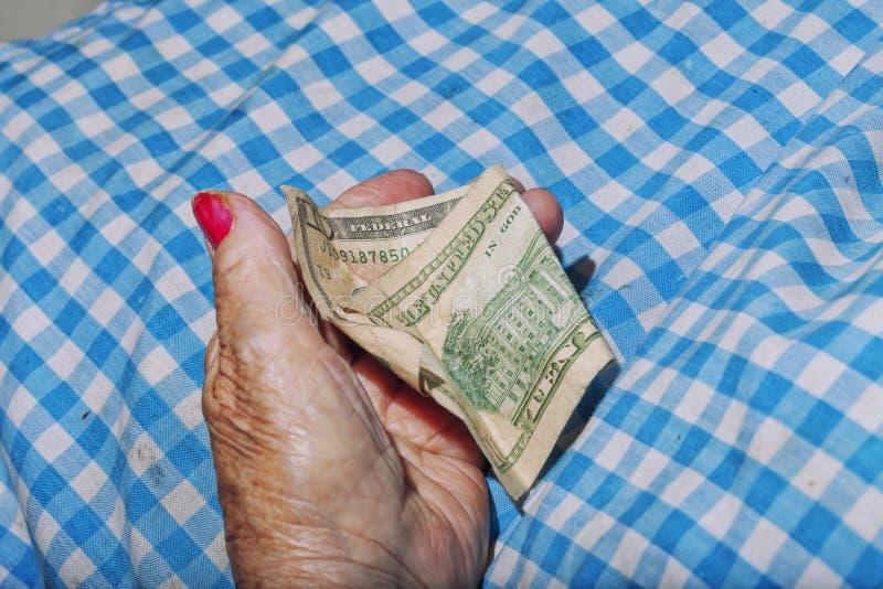Een oude vrouw met een oude tien dollarrekening stock foto