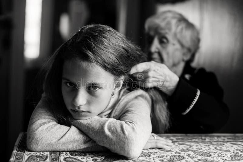 Een oude vrouw vlecht het haar van haar groot-kleindochter royalty-vrije stock foto's