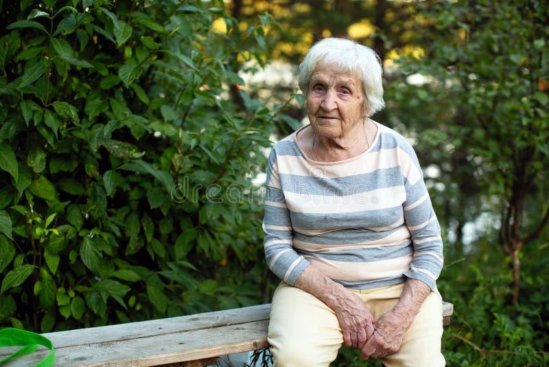 Een oude vrouwenzitting op een houten bank in het Park stock foto