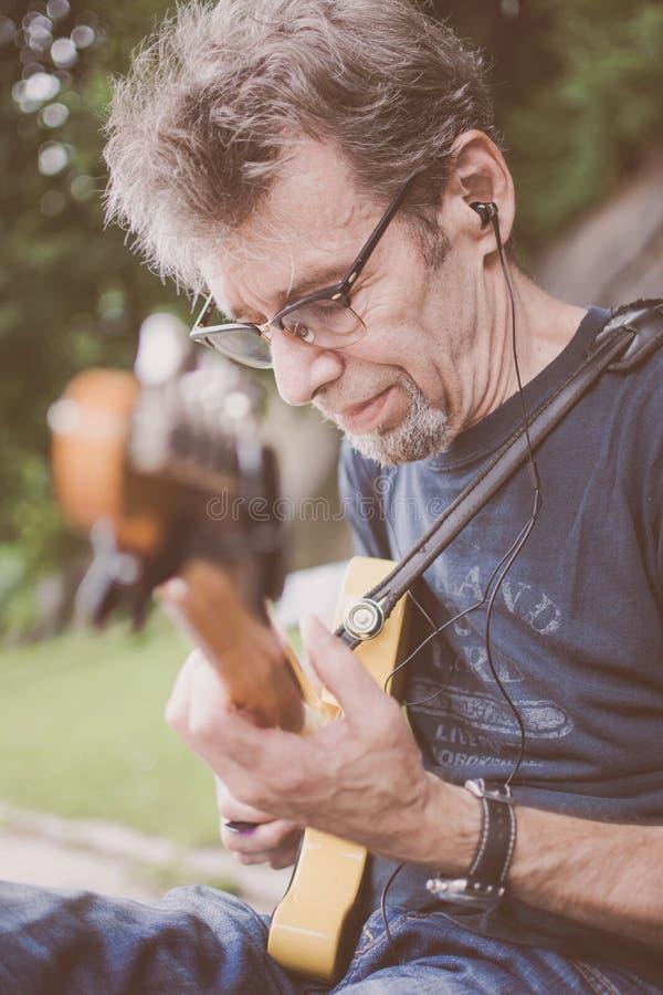 Een oudere mannelijke musicus het spelen gitaar op een de Stadsstraat van New York stock foto's