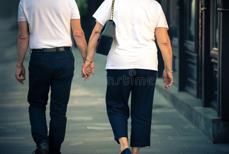 Een oudere vrouw en een man lopen rond de stad in de de zomer en greephanden royalty-vrije stock afbeeldingen