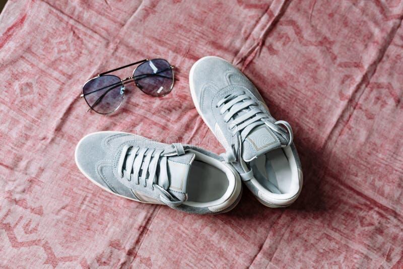 Een paar blauwe suèdetennisschoenen op een witte zool met witte accenten en zonnebril met blauwe glazen op een roze achtergrond royalty-vrije stock afbeelding