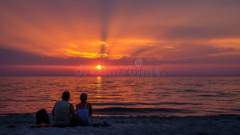 Een paar die op de zonsondergang letten stock afbeelding