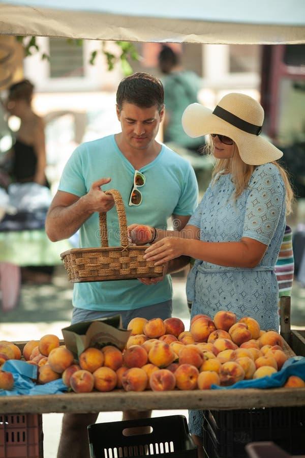 Een paar die perziken krijgen bij de markt stock fotografie