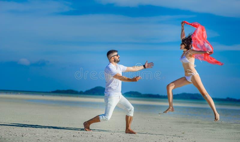 Een paar die pret op strand hebben Witte t-shirt, witte broeken en zonnebril Witte bikini, blootvoets op wit zand royalty-vrije stock foto's