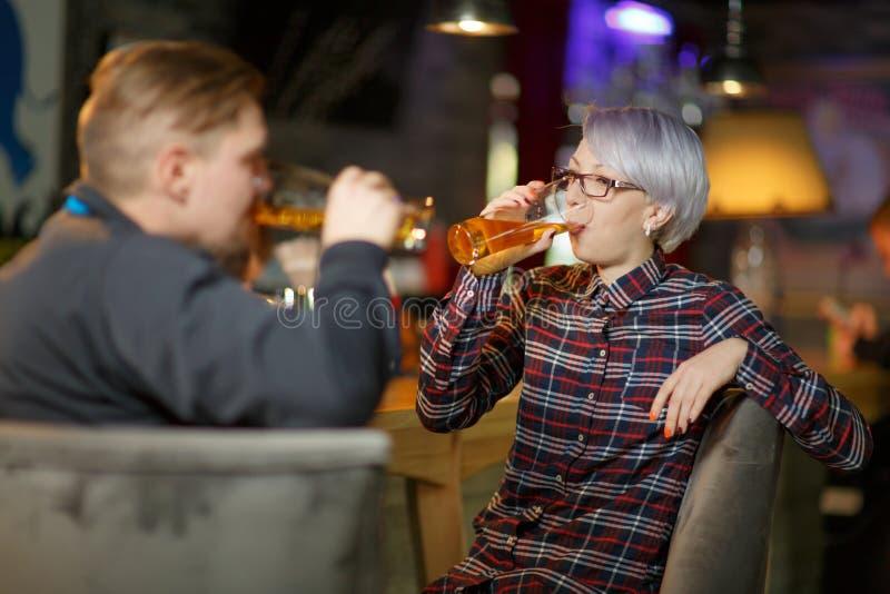 Een paar drinkt bier in een bar Binnen in een openbare ruimte royalty-vrije stock fotografie