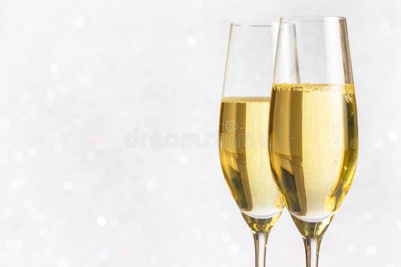 Een paar fluiten van gouden champagne op zilveren bokeh royalty-vrije stock fotografie