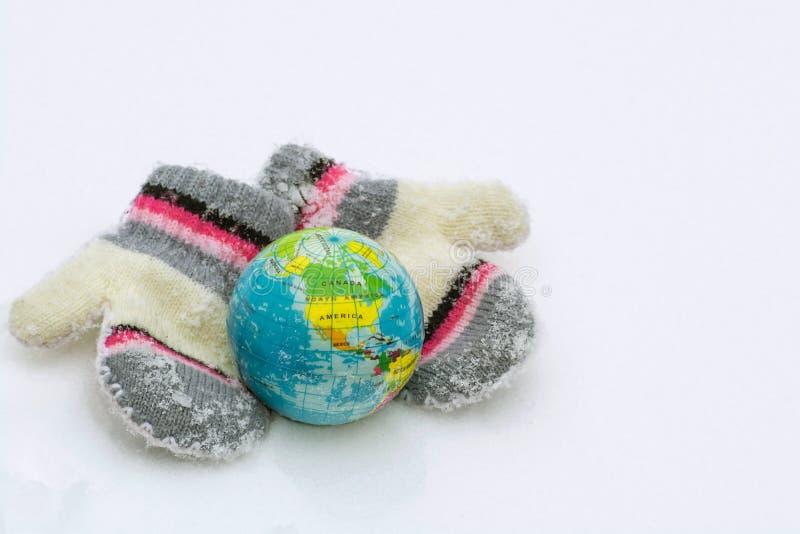 Een paar gebreide vuisthandschoenen beschermt zorgvuldig de aardebol tegen de koude royalty-vrije stock foto