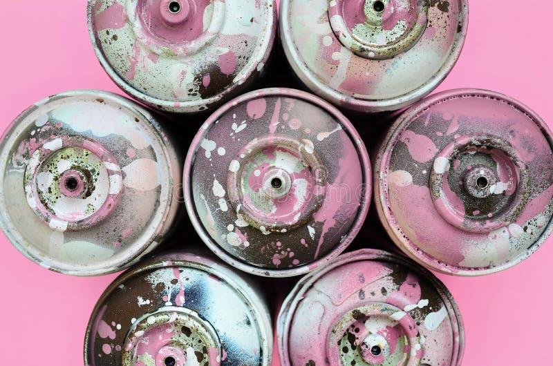Een paar gebruikte aërosols met roze verfdruppels liggen op textuurachtergrond van roze de kleurendocument van de manierpastelkle royalty-vrije stock foto's