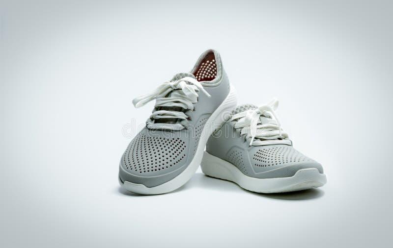 Een paar grijze schoenen op witte achtergrond Comfortabele schoenen met poriën Breedte rubberen schoenen Schoeisel stock afbeeldingen
