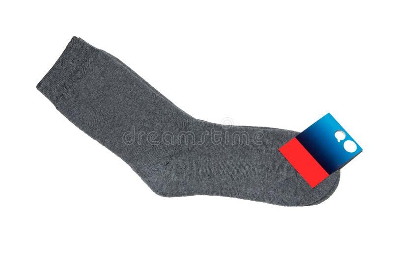 Een paar grijze sokken met een prijskaartje op een grijze achtergrond stock fotografie