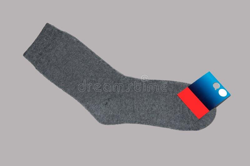 Een paar grijze sokken met een prijskaartje op een grijze achtergrond stock afbeelding