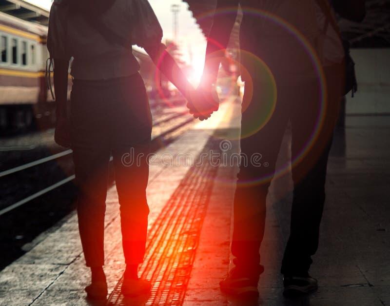 Een paar handen lopen samen op het treinstation royalty-vrije stock fotografie