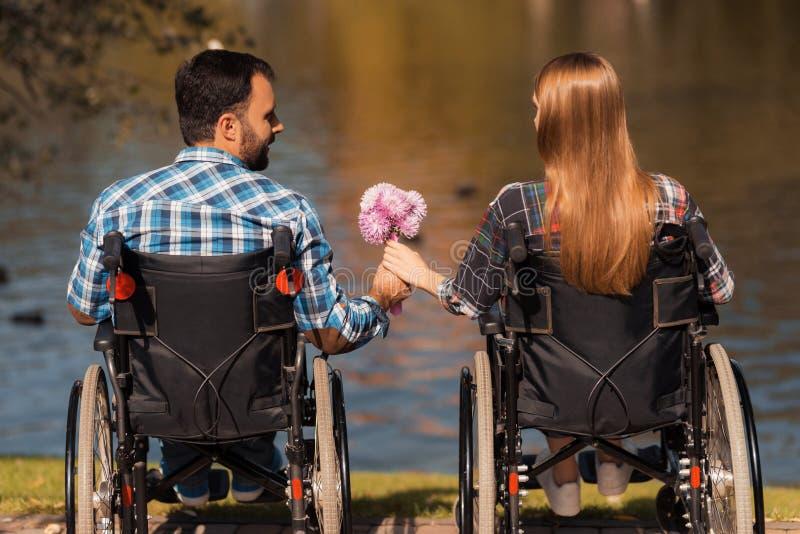 Een paar invalids op rolstoelen kwamen in het park samen Een man en een vrouw houden een boeket van bloemen royalty-vrije stock fotografie