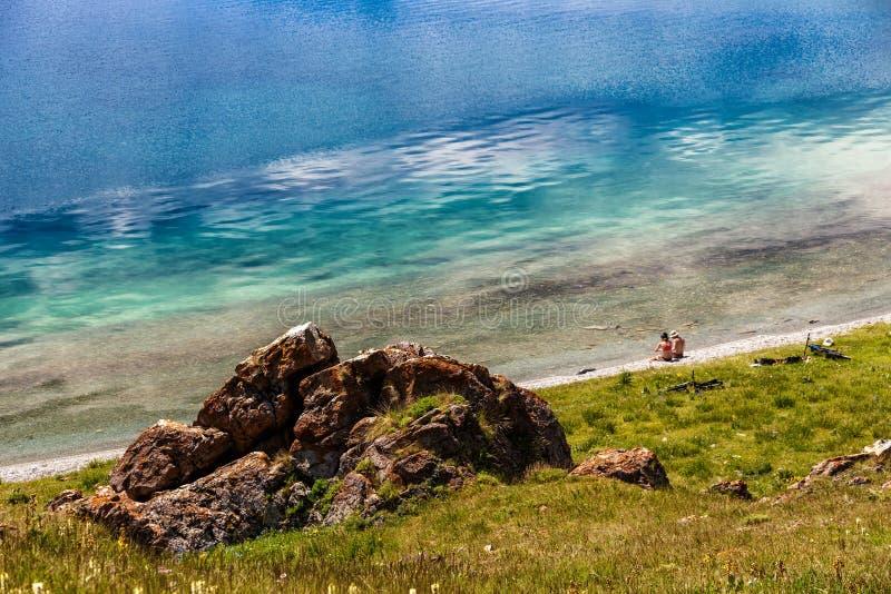 Een paar jongeren met fietsen rust op de kust van een bergmeer stock fotografie