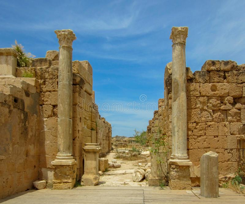 Een paar lange kolommen tegen steenmuren onder een blauwe hemel bij oude Roman ruïnes van Leptis Magna in Libië royalty-vrije stock foto's