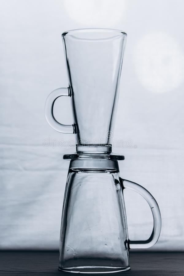 Een paar lege transparante glasglazen op een grijs zilveren close-up als achtergrond twee lange mokken met een handvat en een bee royalty-vrije stock fotografie