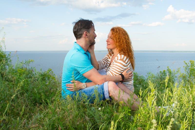 Een paar in liefde openlucht Minnaars zitten gekoesterd op het gras bij meerbank in gras op water en hemelachtergrond stock afbeelding