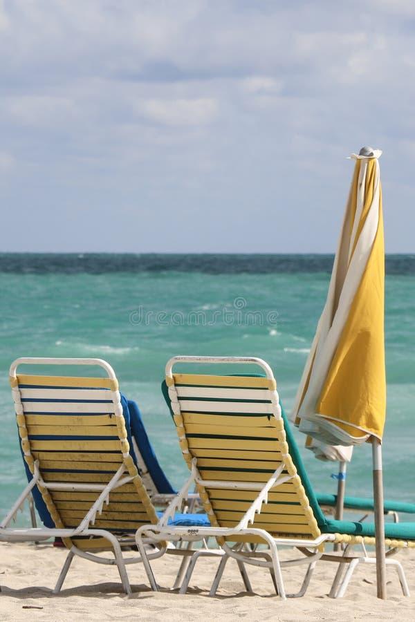 Een paar ligstoelen en gele umbrela in het strand van Miami stock foto