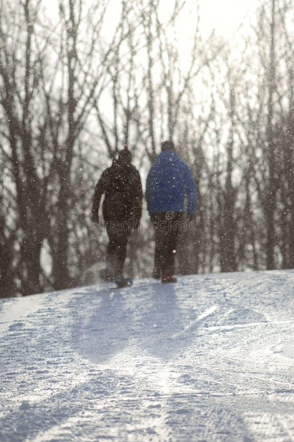 Een paar loopt omhoog een sneeuwweg royalty-vrije stock foto's