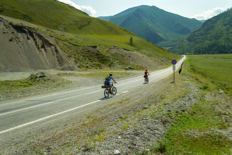 Een paar man en vrouw in helmen berijden op sportenfietsen stock foto's
