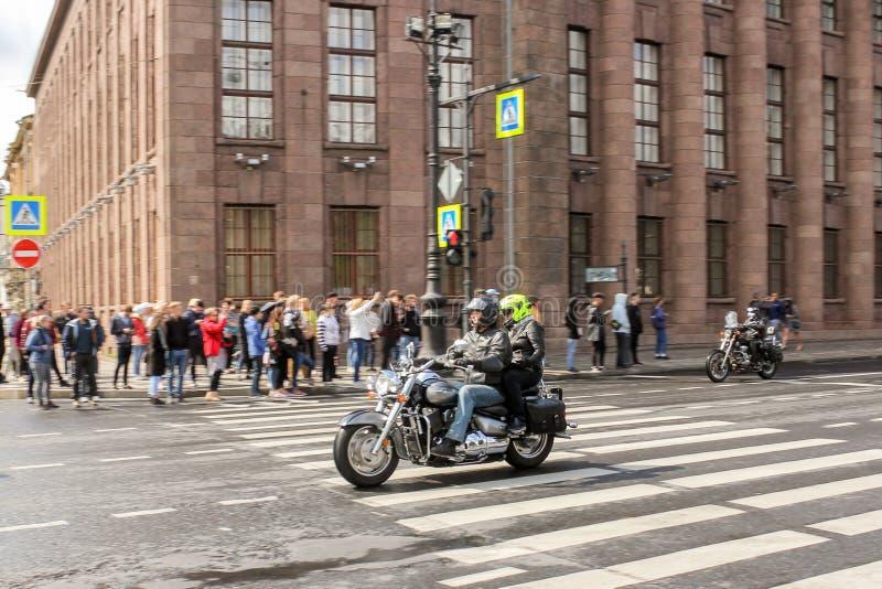 Een paar motorrijders gaat door toeschouwers over stock fotografie