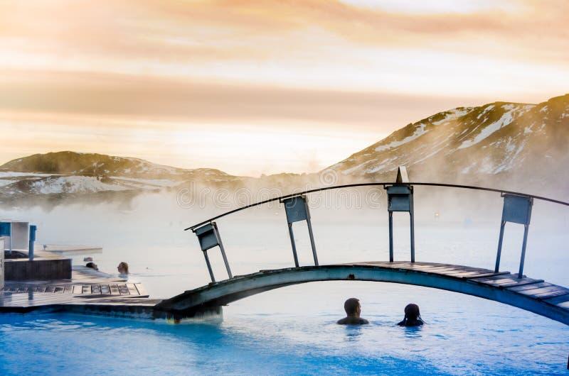 Een paar onder de brug in de thermische blauwe lagune, IJsland stock fotografie