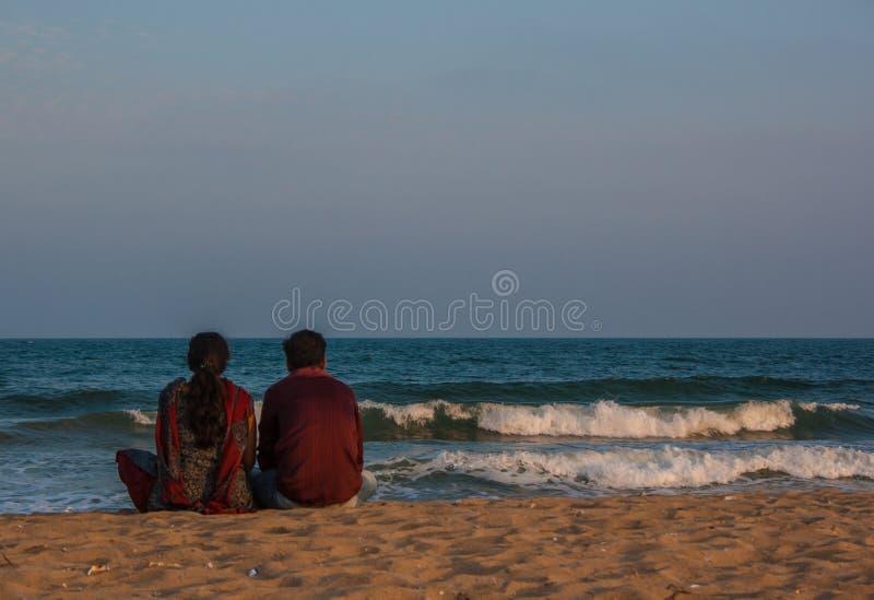 Een paar ontspant op het strand stock fotografie