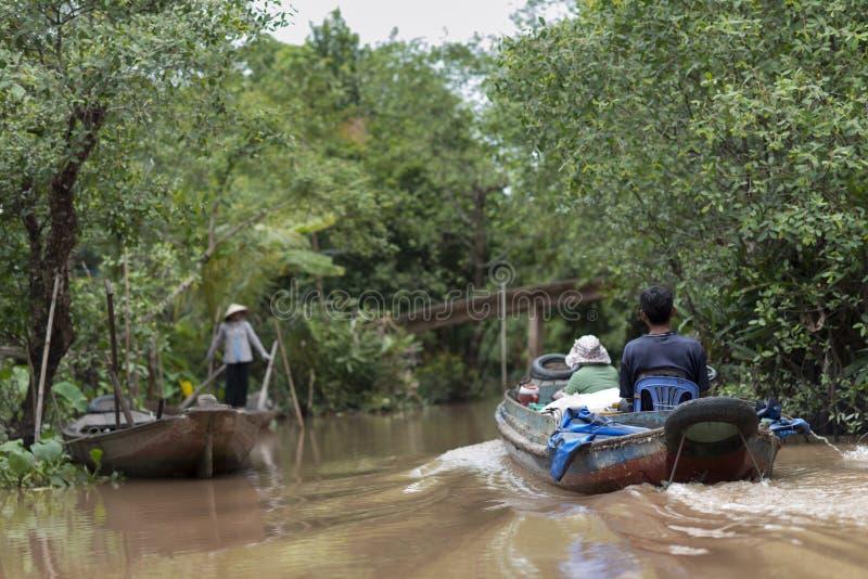 Een paar op een kleine boot op de Mekong rivier, Vietnam stock fotografie