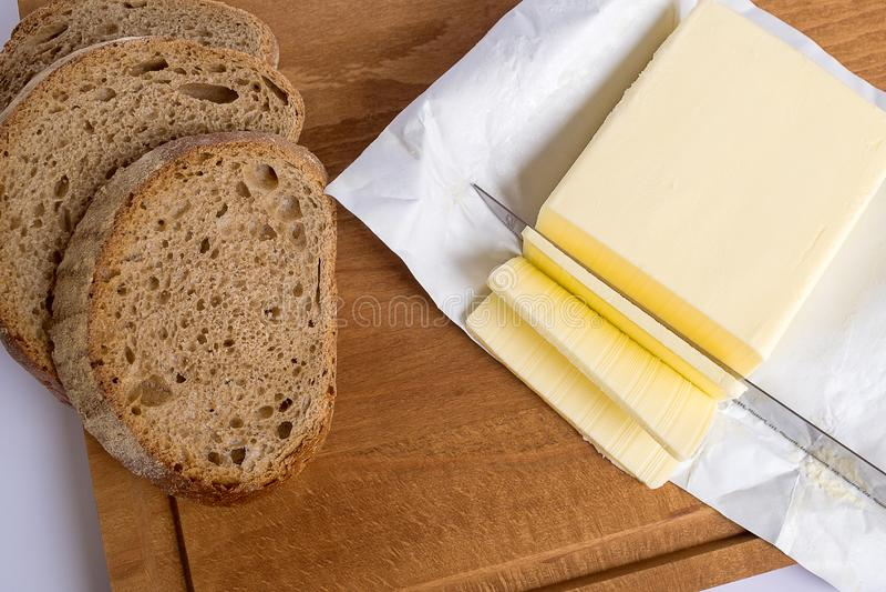 Een paar plakken van gele die boter van een brok met een mes op een bruine houten scherpe raad worden afgesneden Verscheidene pla royalty-vrije stock foto's