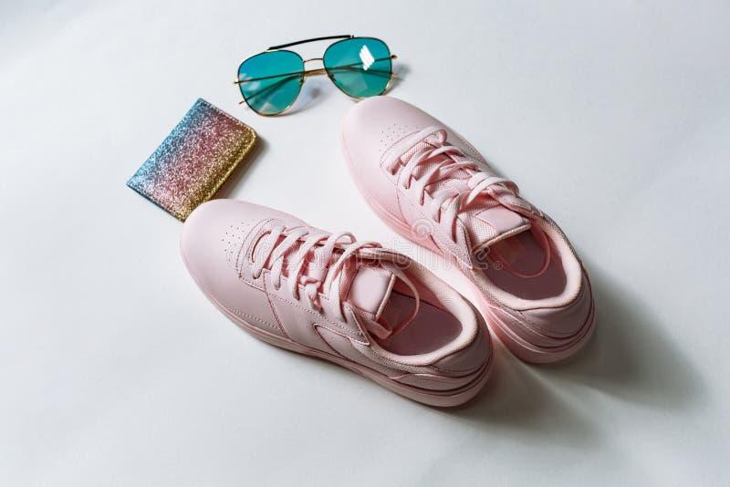 Een paar roze leertennisschoenen, een beurs met multi-colored lovertjes en zonnebril met blauw glas op een witte achtergrond royalty-vrije stock afbeelding